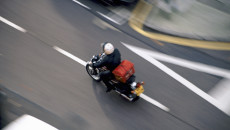 Motorcycle courier speeding along a road from above, London W14, England